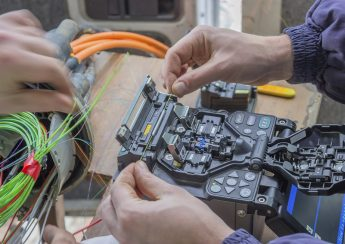 Fibre optic technician splicing fibers. Splicing two fibers using the fusion splicer.